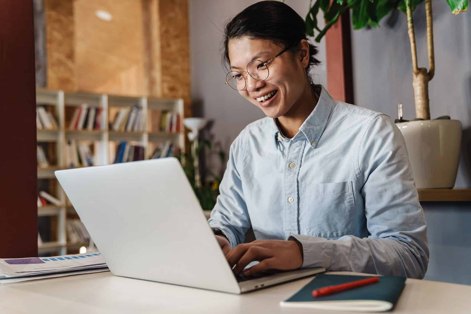 Woman smiling and working on laptop